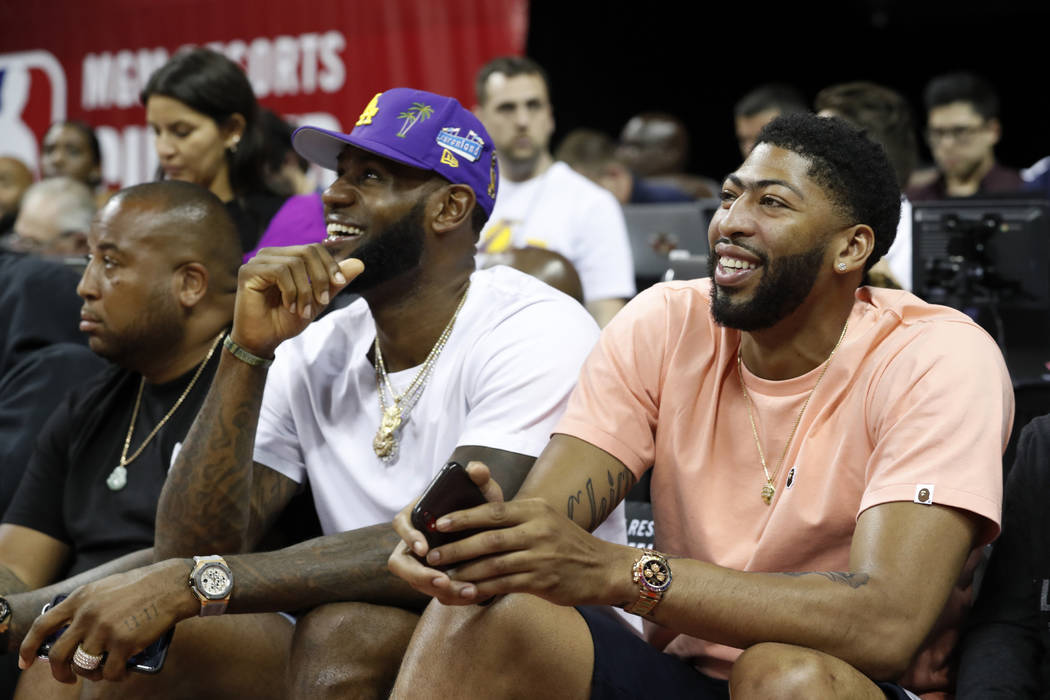 Los Angeles Laker players LeBron James, center, and Anthony Davis, right, take in an NBA summer ...