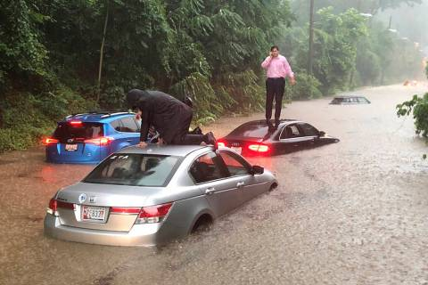 Motorists are stranded on a flooded section of Canal Road in Washington during a heavy rainstor ...
