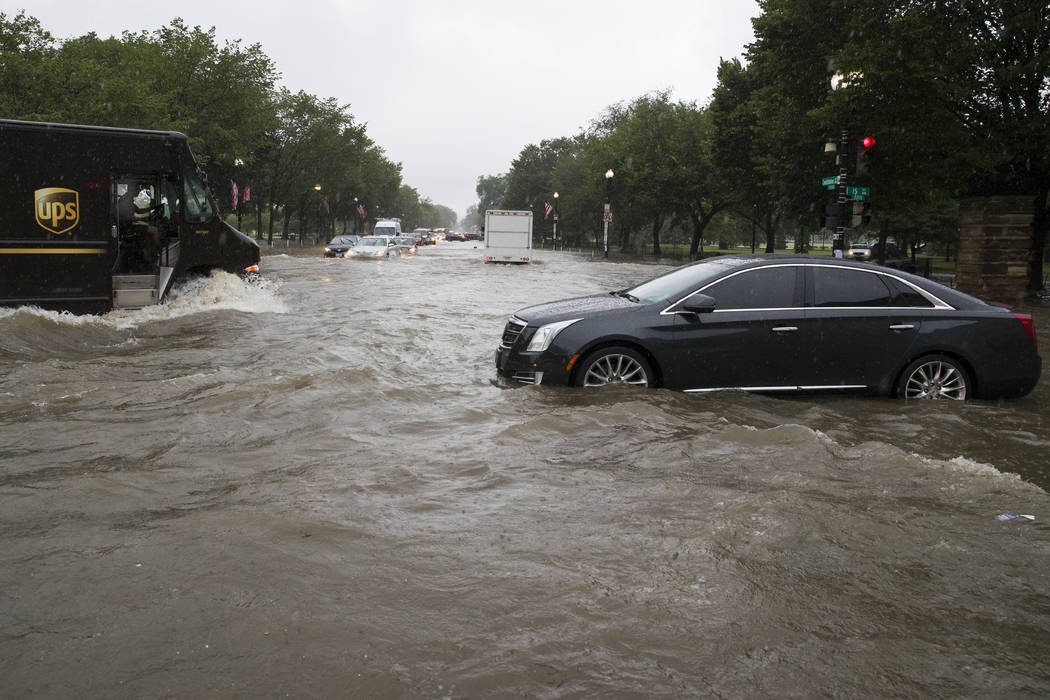 Heavy rainfall flooded the intersection of 15th Street and Constitution Ave., NW stalling cars ...