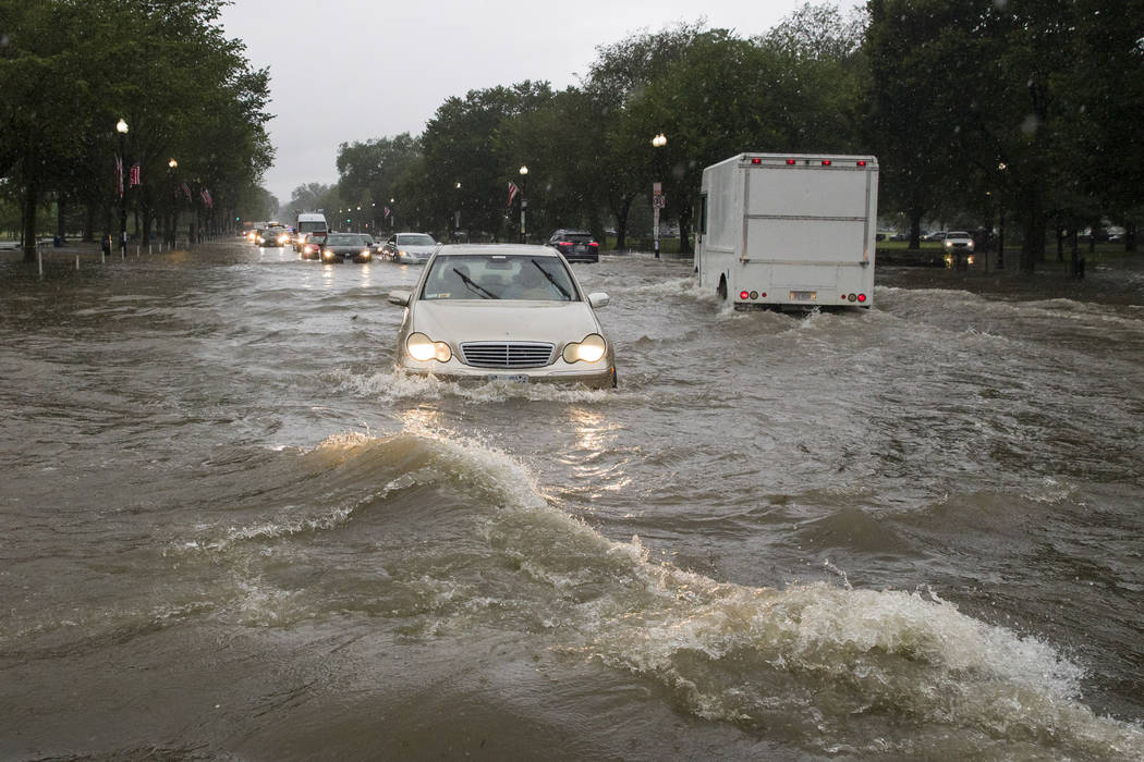 Heavy rainfall flooded the intersection of 15th Street and Constitution Ave., NW, stalling cars ...