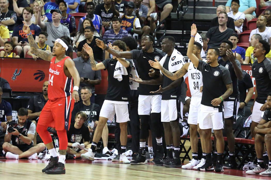 The Washington Wizards' guard Troy Caupain (14) and the Brooklyn Nets' bench players protest a ...
