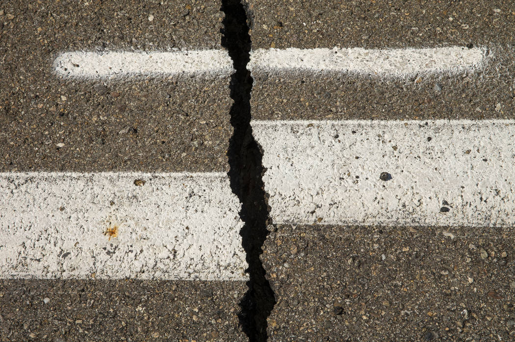 Caltrans workers continue to monitor the extensive cracks with shifting pavement that have open ...