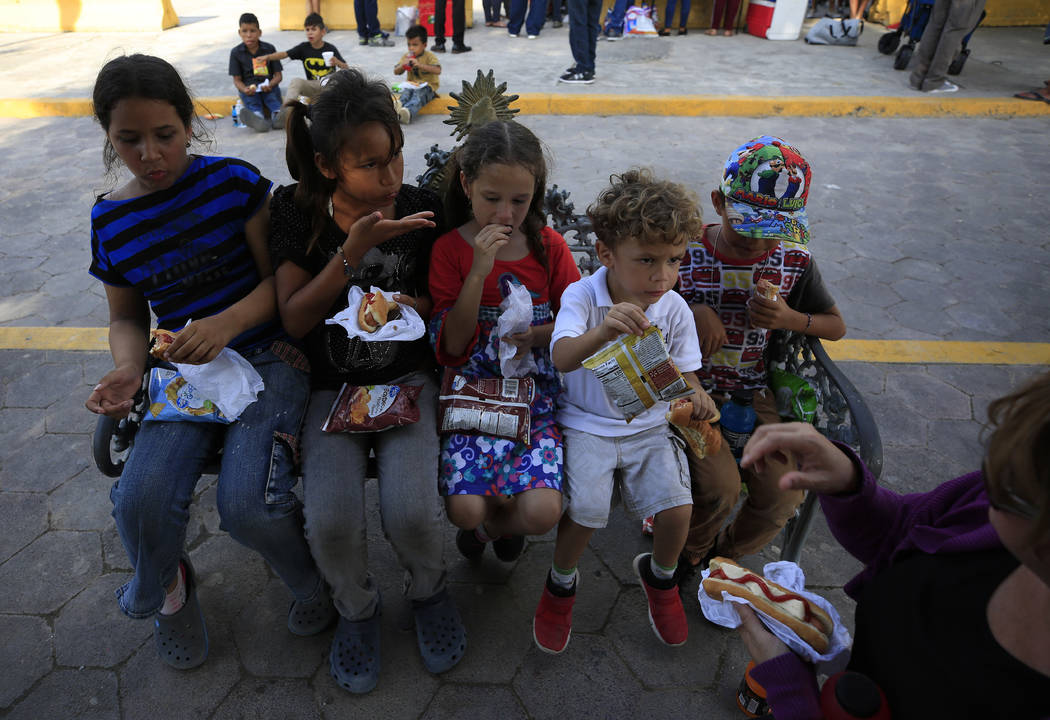Migrant children eat a meal provided by United in Christ Ministry of Los Fresnos, Texas, a grou ...