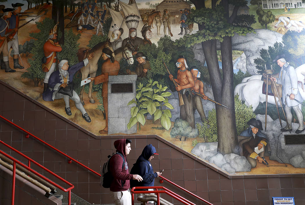 In this photo taken April 3, 2019, a pair of students walk past a historic mural that includes ...