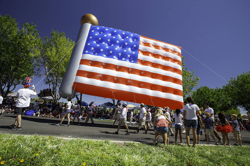 The parade featured traditional floats, giant inflatable balloons, American military heroes, ba ...