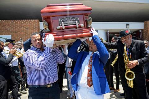 Pallbearers carry the coffin of Dave Bartholomew past the Treme brass band as they exit St. Gab ...