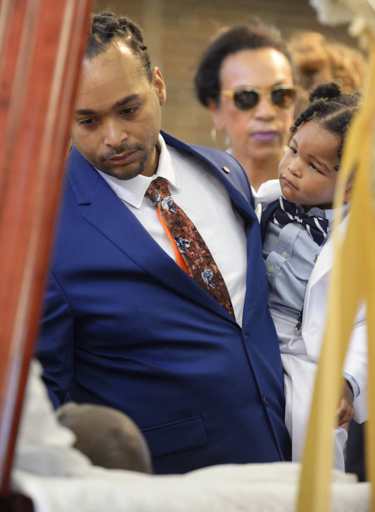 Don Bartholomew Jr., with son Lyric, looks at the body of Dave Bartholomew during the viewing a ...