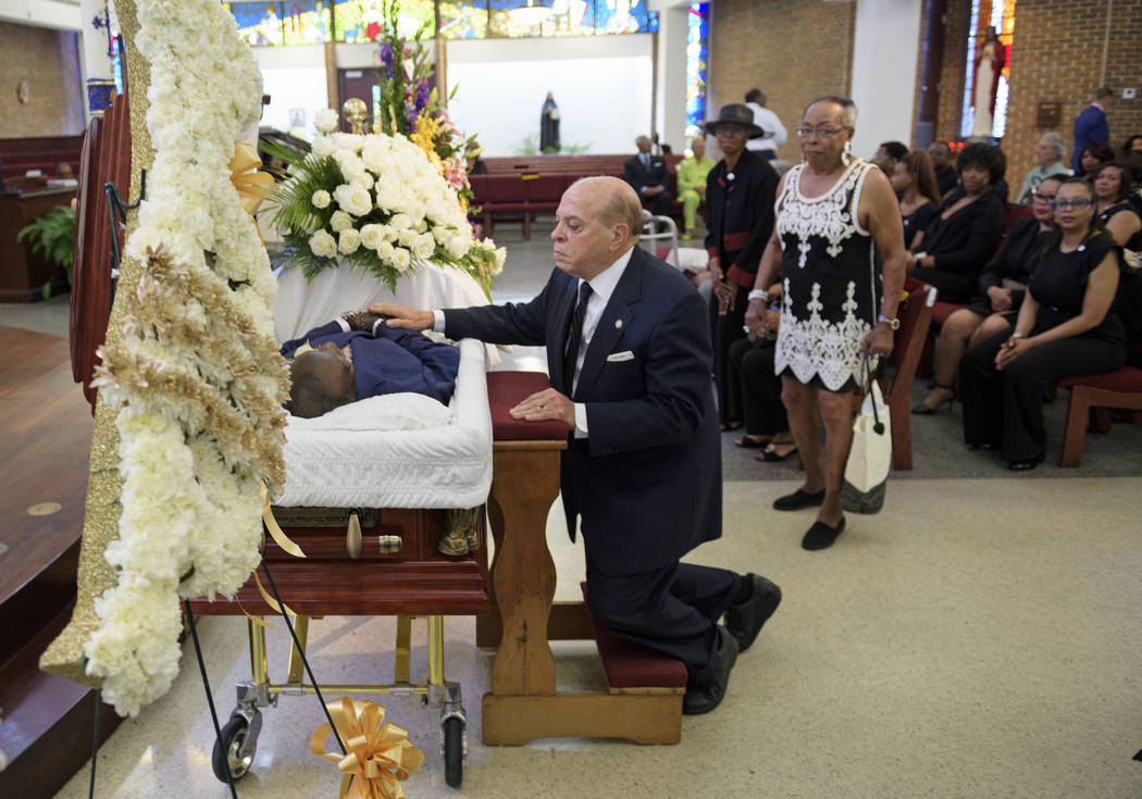 Deacon John Moore touches his friend for the last time during the viewing of Dave Bartholomew a ...
