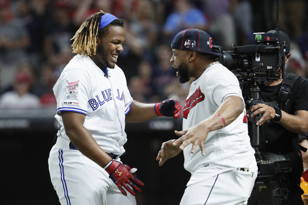 Vladimir Guerrero Jr., left, of the Toronto Blue Jays, is greeted by Carlos Santana, of the Cle ...