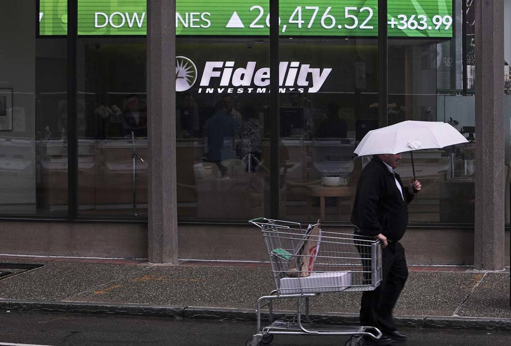 In a June 18, 2019, photo a man pulls a grocery cart as he walks in the rain past the stock tic ...