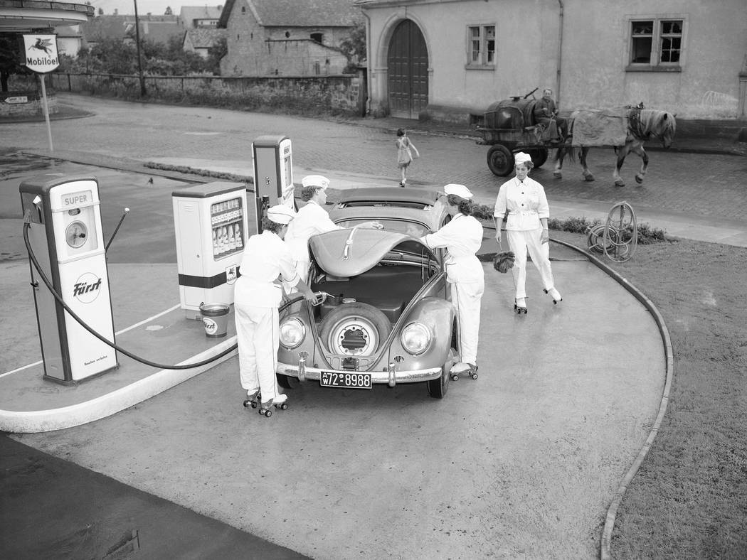FILE - In this Aug. 23, 1954 file photo, four female employees tend to a Volkswagen at a gas st ...