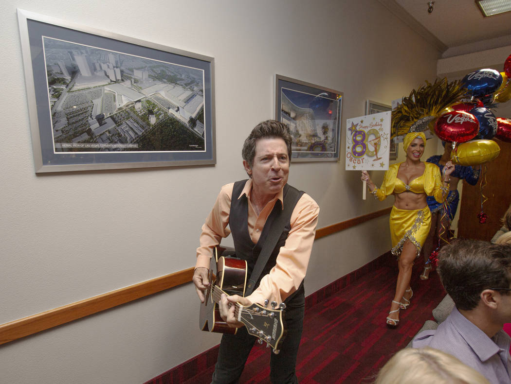Elvis Impersonator Gregg Peterson plays guitar as showgirl Jennifer Gagliano, background,& ...