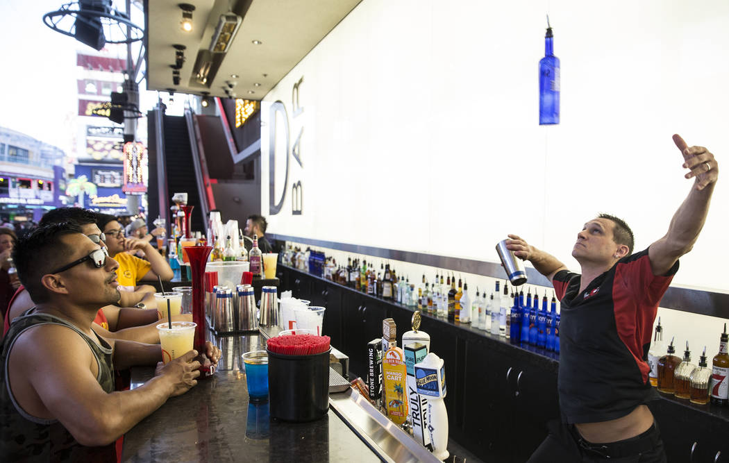 Bartender Kristian Mihailin, right, wows the crowd while making a frozen specialty drink at D B ...