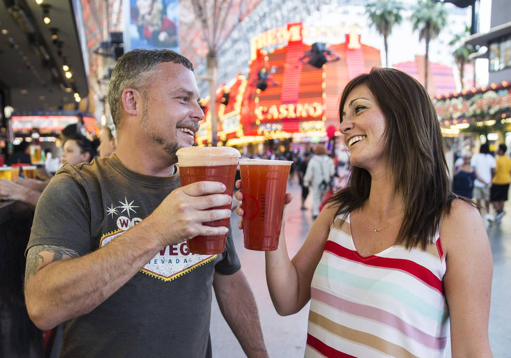 Kevin Thomason, left, and Melissa Bennett celebrate after ordering 32-ounce red beers on Friday ...