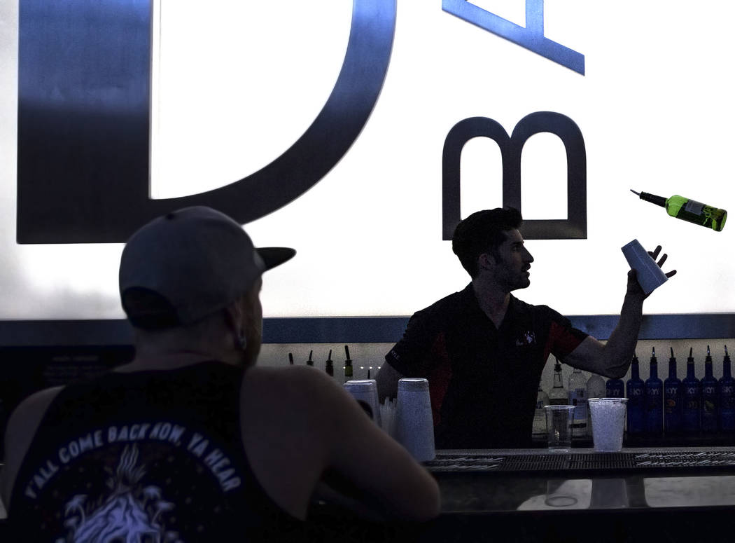 Kyle Poli, right, shows off his flair bartending skills while making a frozen specialty drink a ...
