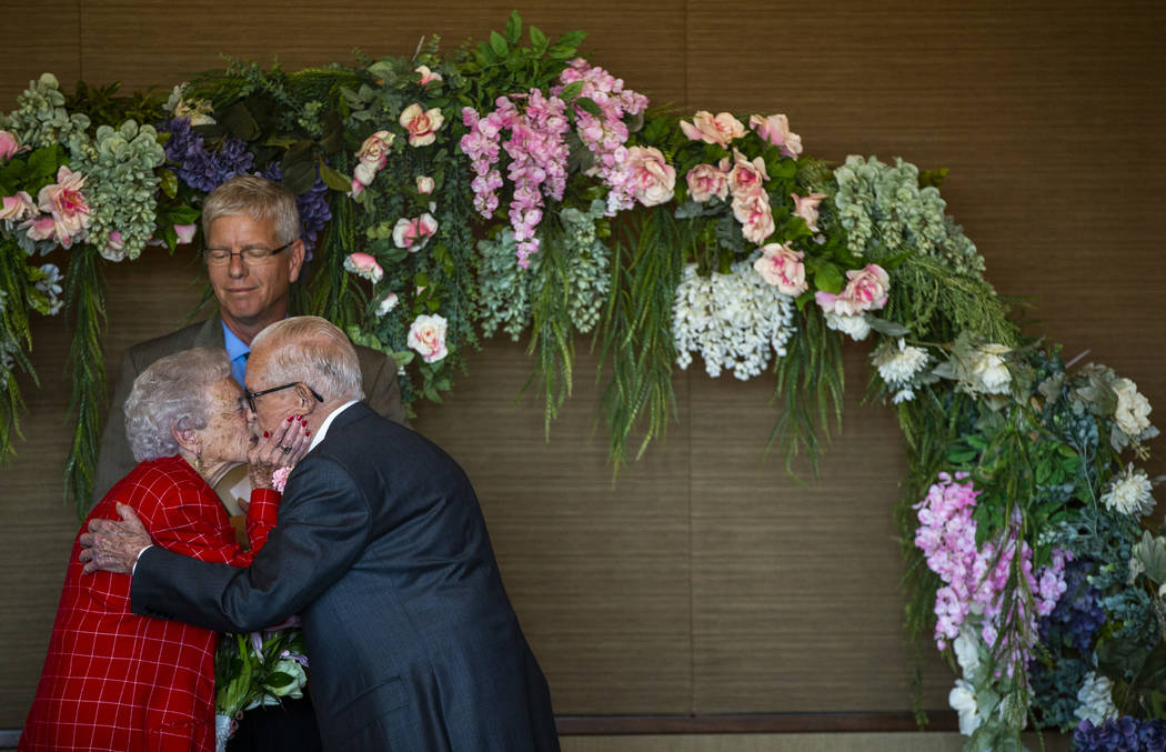 Donna Andress kisses her husband, Gail, right, as Deacon Tim O'Callaghan presides during a rene ...