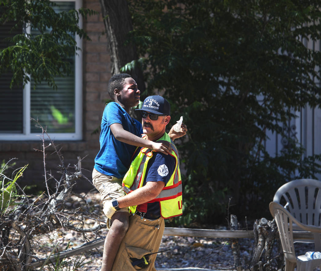 A firefighter carries one of the children injured in a crash on West Washington Avenue near Dec ...