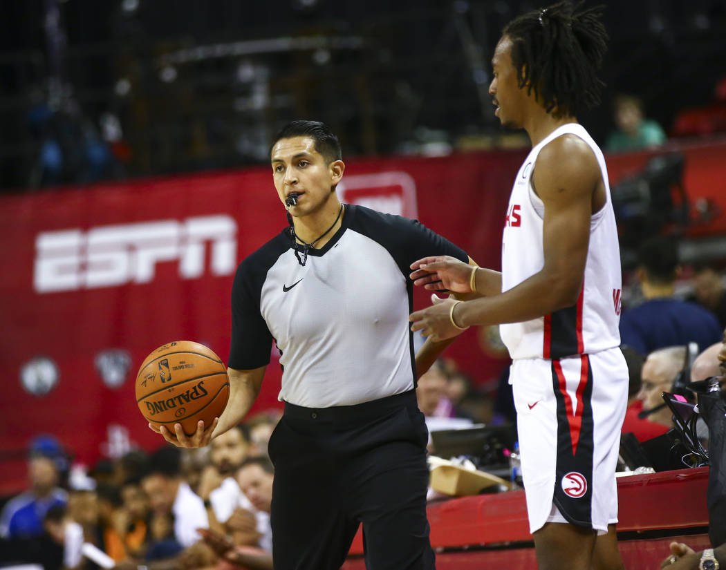 Referee Omar Bermudez, left, stands next to Atlanta Hawks' Tahjere McCall while officiating a g ...