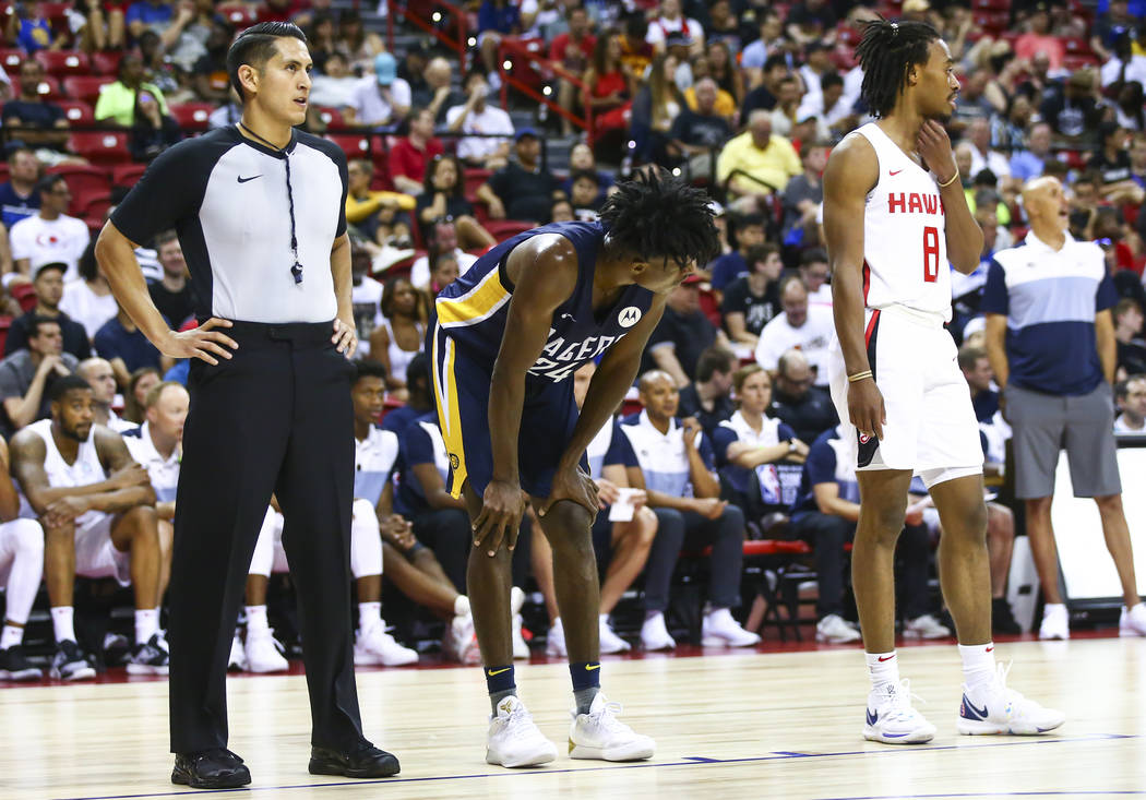 Referee Omar Bermudez, left, stands to watch a free throw attempt while officiating a game betw ...