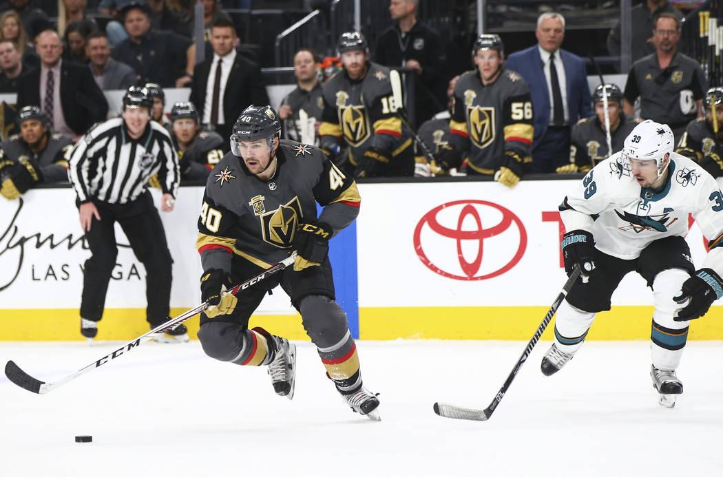 Golden Knights center Ryan Carpenter (40) skates with the puck as San Jose Sharks center Logan ...
