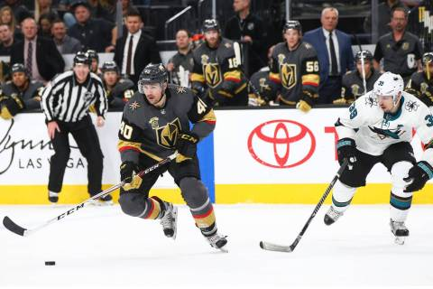 Golden Knights center Ryan Carpenter (40) skates with the puck as San Jose Sharks center Logan ...