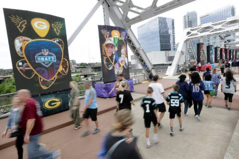 People walk on a bridge lined with video boards providing news on draft picks on the final day ...