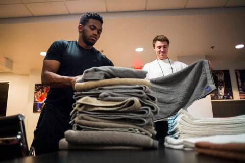 UNLV students Wesley Wharton, left, and Devin James organize towels for the UNLV basketball tea ...