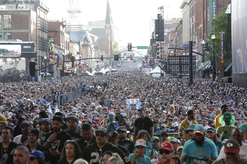 Fans stand near the main stage ahead of the second round of the NFL football draft, Friday, Apr ...