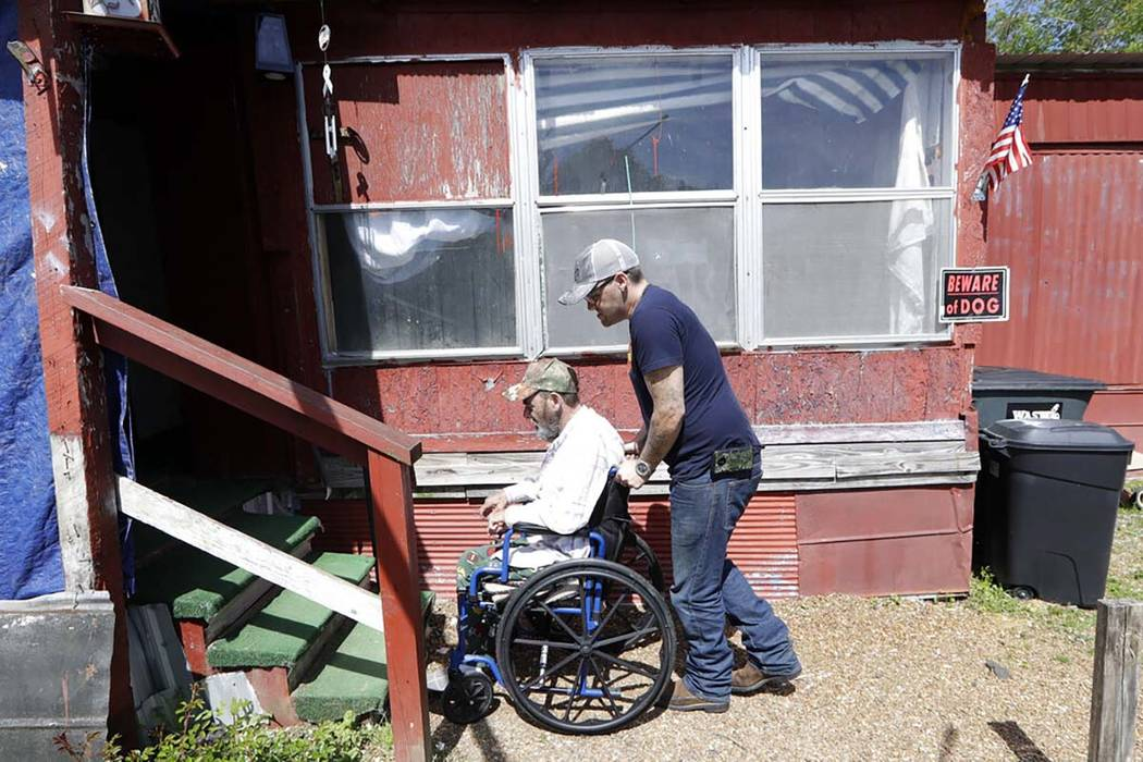 In this April 16, 2019, photo, Johnny Gibbs helps his disabled father, Mike, 65, into their hom ...