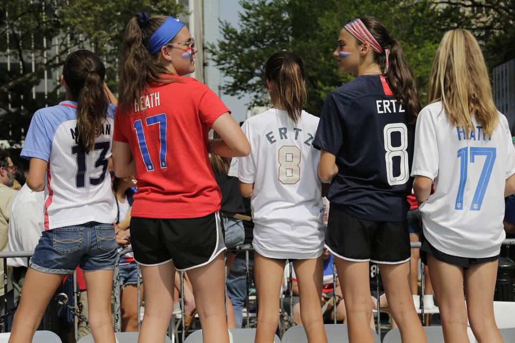 Girls in soccer jerseys wait for the arrival of the U.S. women's soccer team at City Hall, afte ...