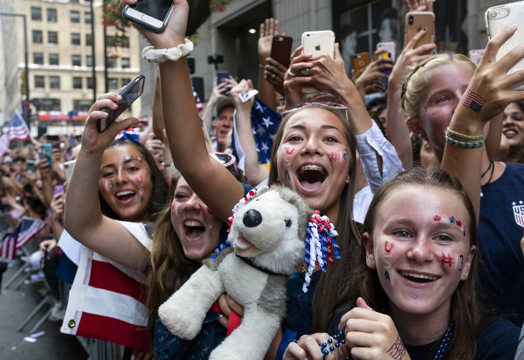 Fans celebrates as members of the the U.S. women's soccer team pass by during a ticker tape par ...
