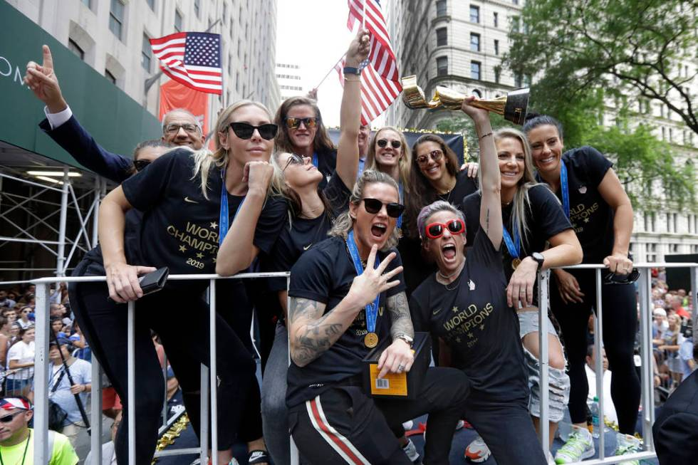 Megan Rapinoe holds the Women's World Cup trophy as the U.S. women's soccer team is celebrated ...