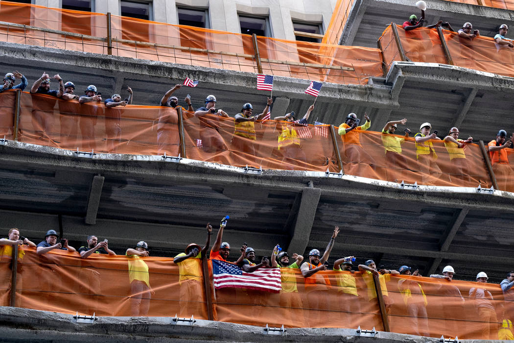 Construction workers watch as members of the U.S. women's soccer team is celebrated with a tick ...