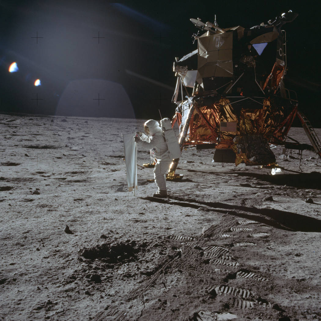Apollo 11 astronaut Buzz Aldrin works on a solar wind experiment device on the surface of the m ...
