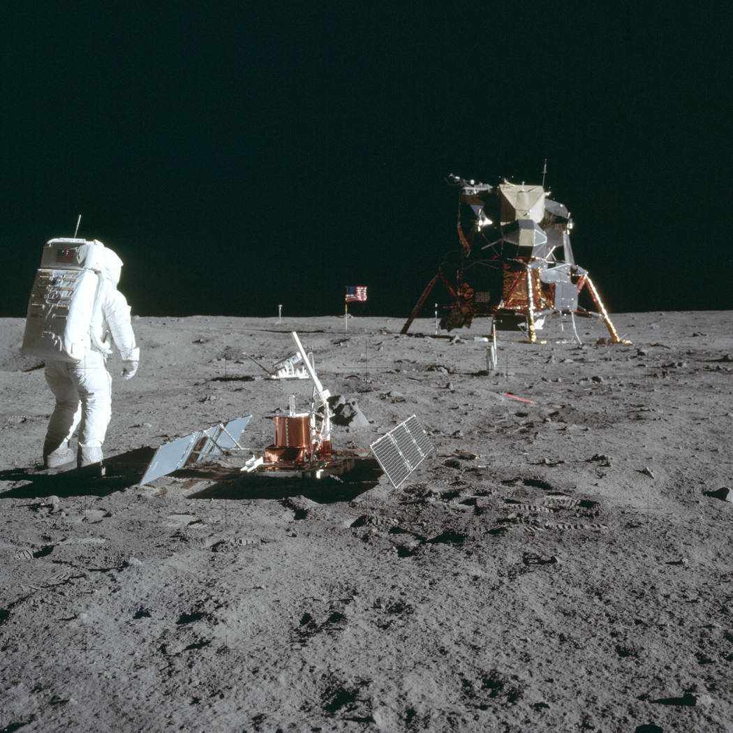 Astronaut Buzz Aldrin Jr. stands next to the Passive Seismic Experiment device on the surface o ...