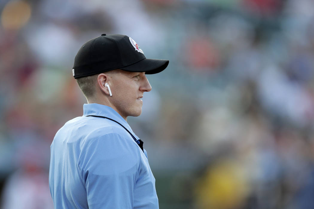 Home plate umpire Brian deBrauwere looks on while wearing an earpiece connected to a ball and s ...