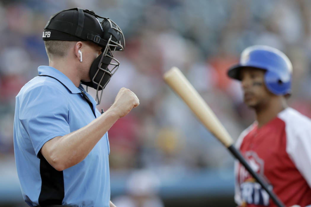 Home plate umpire Brian deBrauwere, left, calls a strike given to him by a radar system over an ...