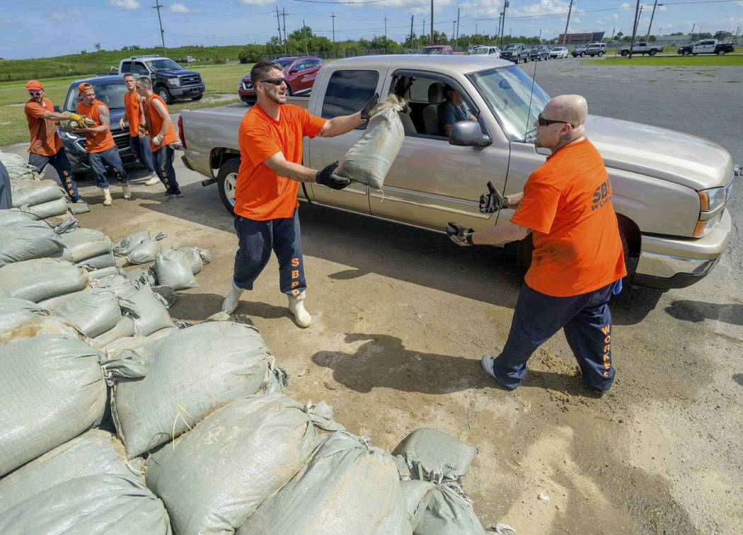 St. Bernard Parish Sheriff's Office inmate workers move free sandbags for residents in Chalmett ...