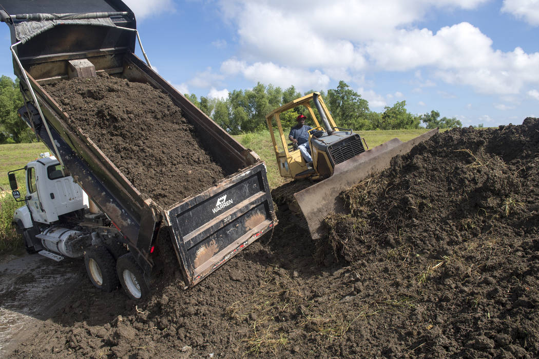 Plaquemines Parish road crews add more dirt to the top of a levee near the Mississippi River le ...
