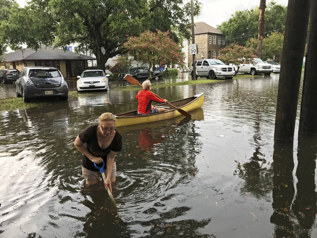 People cope with the aftermath of severe weather in the Broadmoor neighborhood in New Orleans, ...