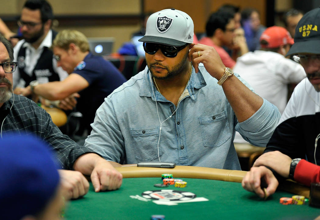 NFL player and poker player Richard Seymour adjusts his ear buds as he plays during Day 1C of t ...