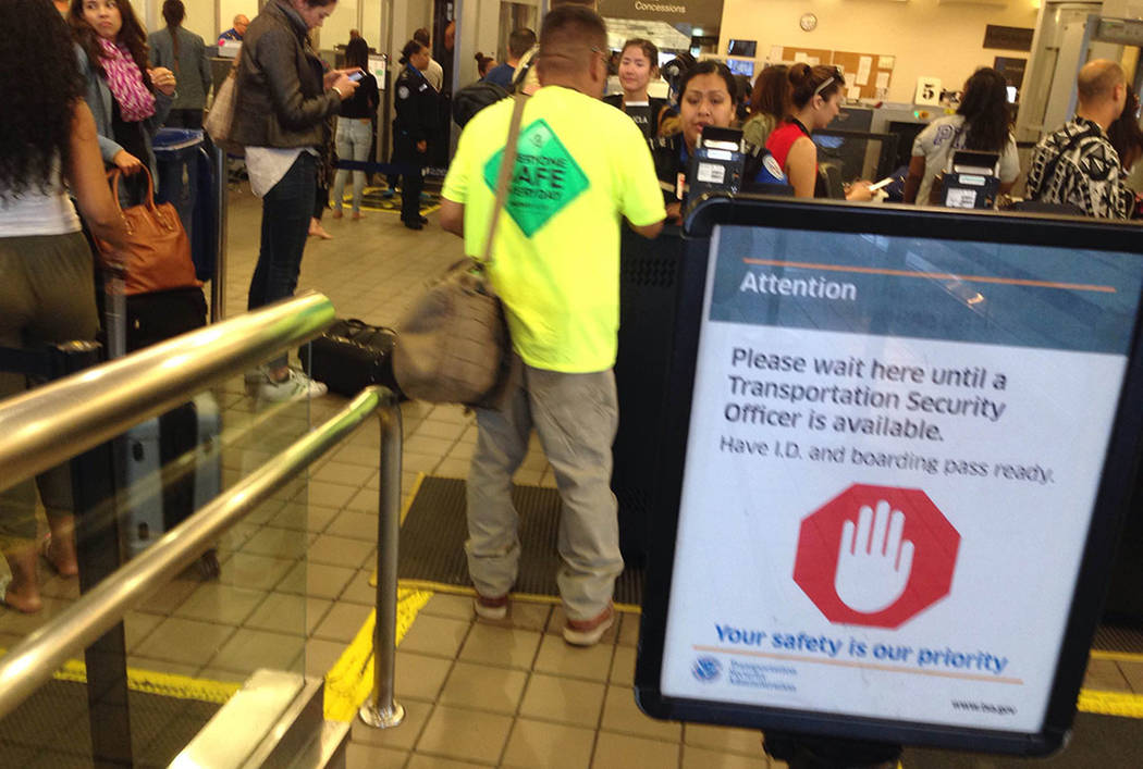 Passengers are screened by Transportation Security Administration workers at McCarran Internati ...
