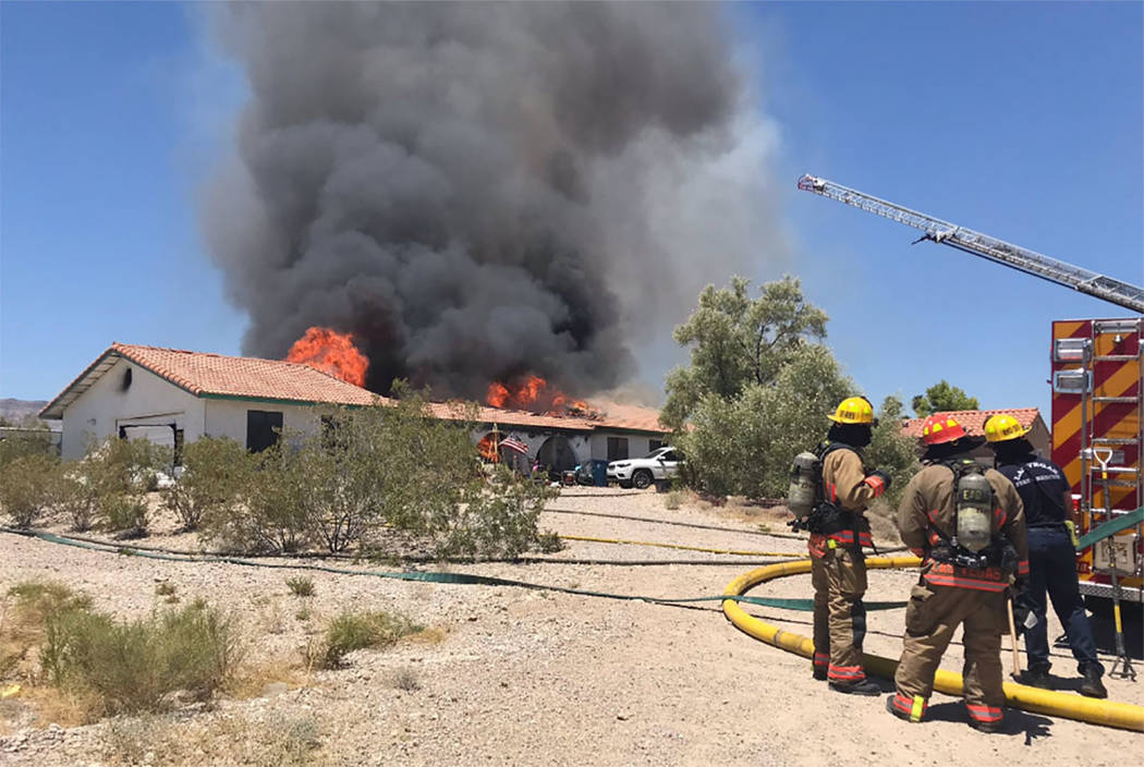 Crews battle a house fire Thursday, July 11, 2019, on the 5300 block of North Fort Apache Road ...