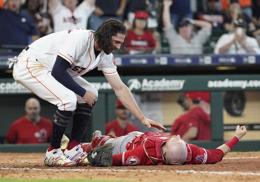 Houston Astros' Jake Marisnick, left, checks on Los Angeles Angels catcher Jonathan Lucroy afte ...