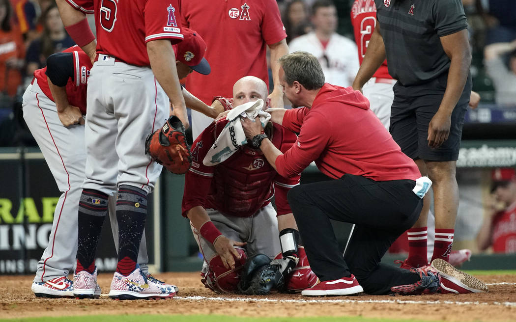 Los Angeles Angels' Jonathan Lucroy, center, is helped by medical personnel after colliding wit ...
