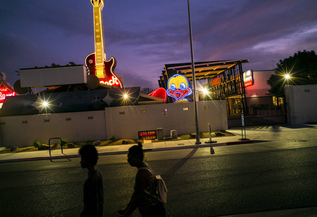 People walk by the recently restored Ugly Duckling sign at the Neon Museum in downtown Las Vega ...