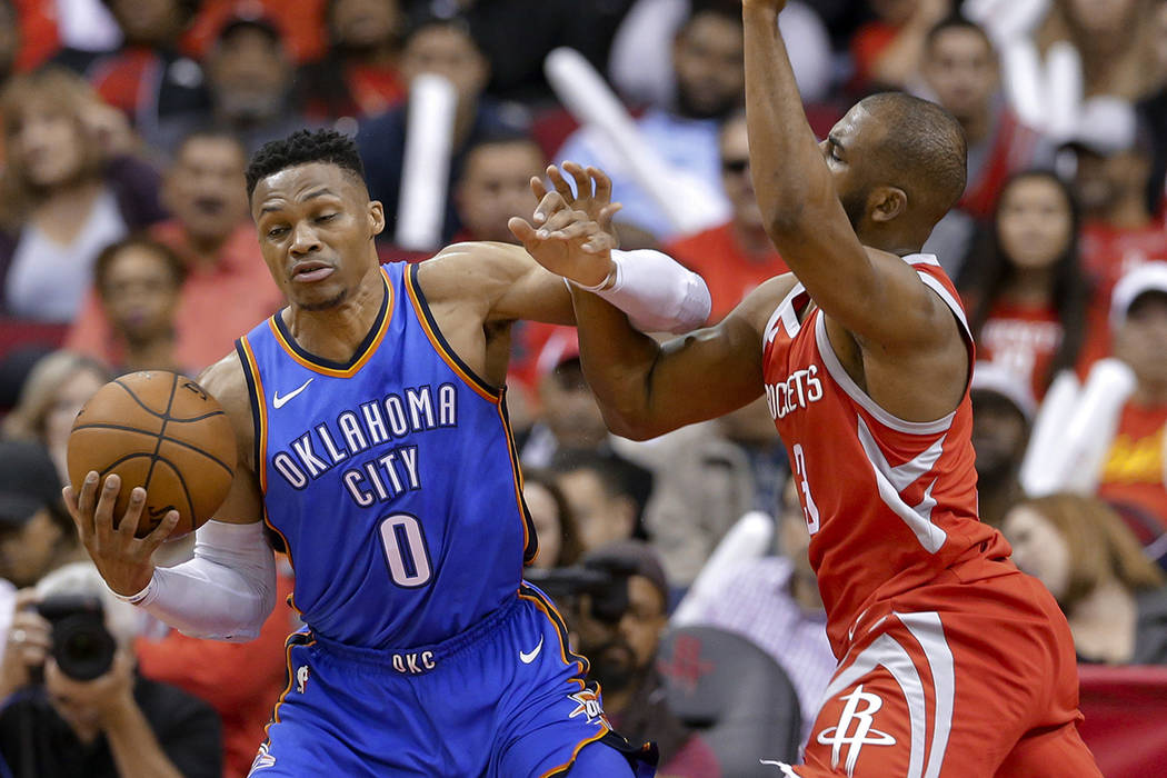 Oklahoma City Thunder guard Russell Westbrook (0) is fouled by Houston Rockets guard Chris Paul ...