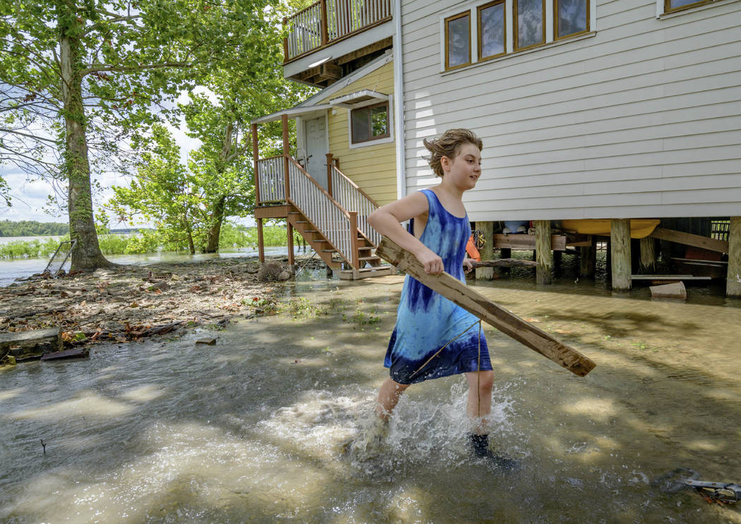 Tallulah Campbell, 8, clears out driftwood and other debris in preparation of Tropical Storm Ba ...