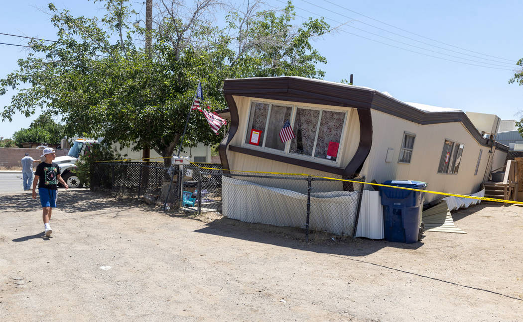 FILE - In this July 5, 2019 file photo, a child walks by one of the mobile homes knocked off it ...