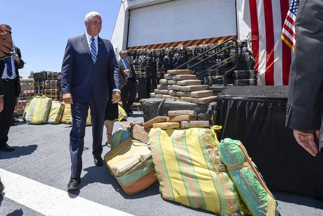 Vice President Mike Pence walks past bales of seized cocaine during a visit to the U.S. Coast G ...